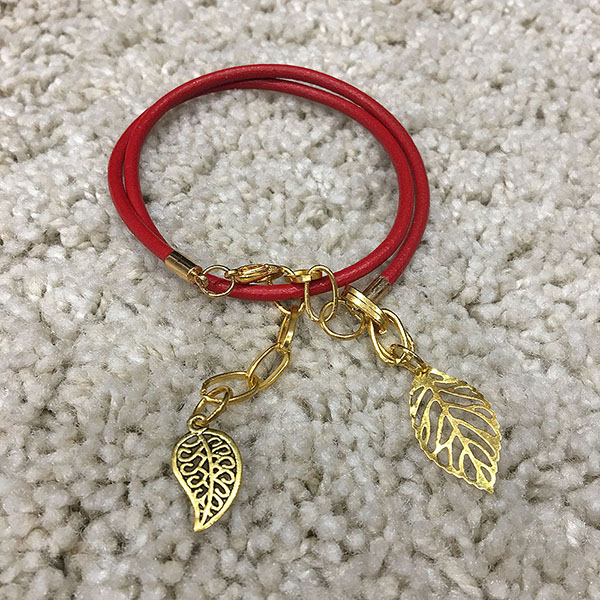 Double twist Red Leather bracelet with a gold plated leaf charm.